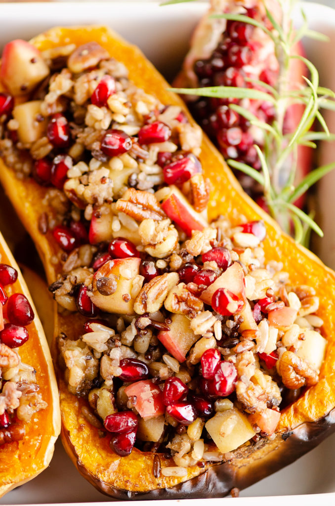 Stuffed Butternut Squash with Apples, Pomegranates & Grains with pomegranate piece and rosemary