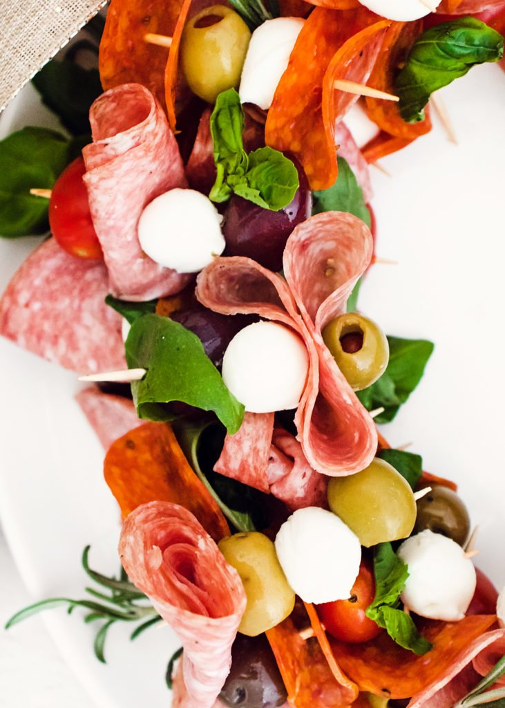 skewers of meat, cheese, olives, tomatoes and basil on white plate
