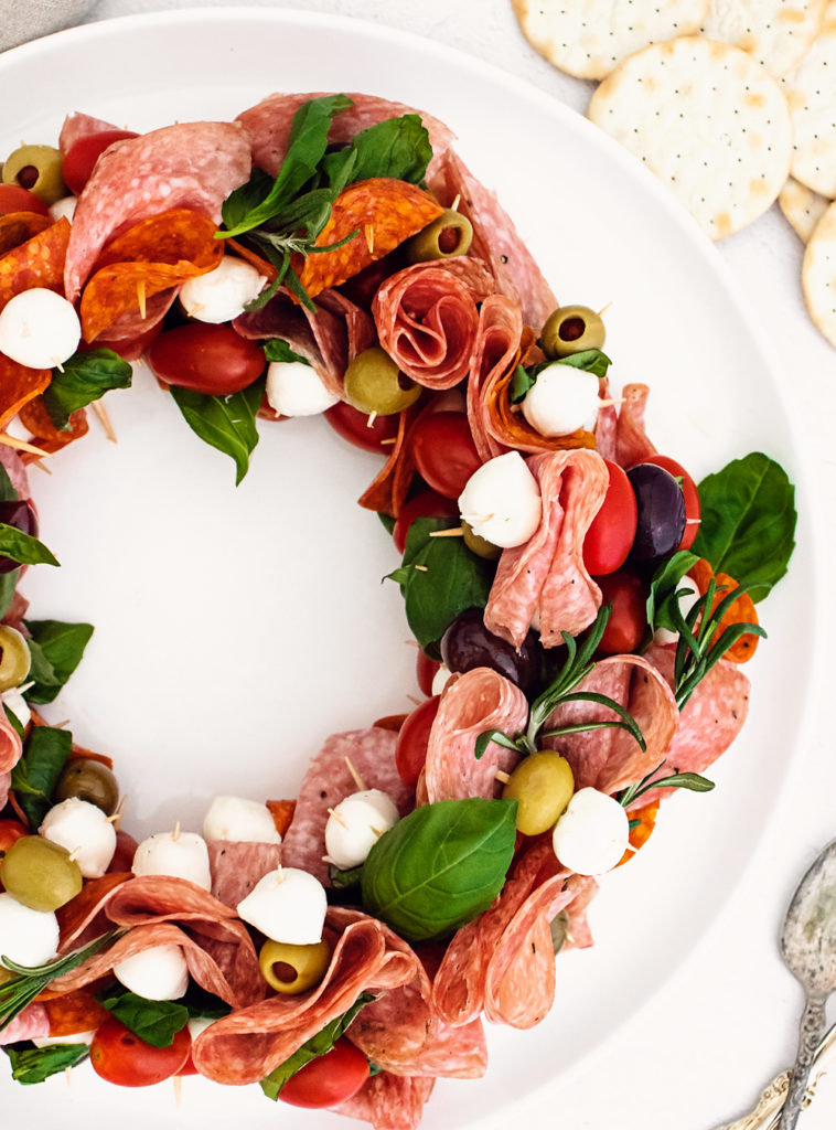 christmas antipasto wreat on white plate served with crackers