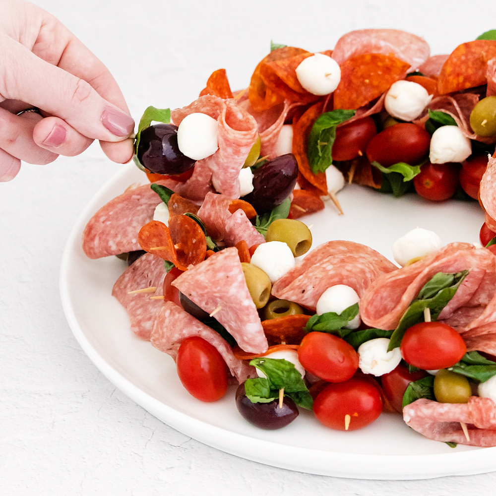 christmas wreath appetizer on plate with skewers of meat and cheese