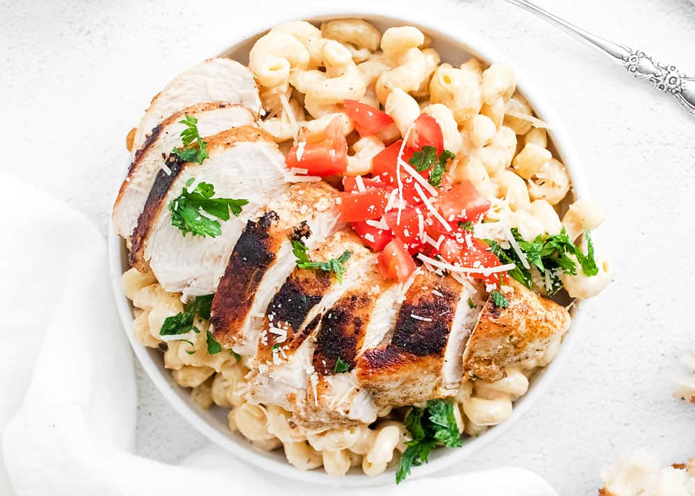 cajun chicken breasts sliced over alfredo pasta in white bowl topped with tomatoes