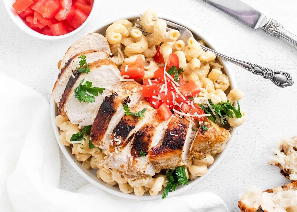 cajun chicken breasts sliced over alfredo pasta in white bowl