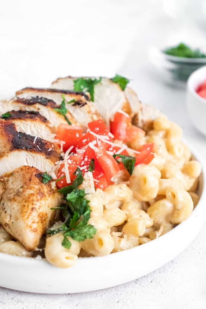 cajun chicken breasts sliced over alfredo pasta topped with tomatoes