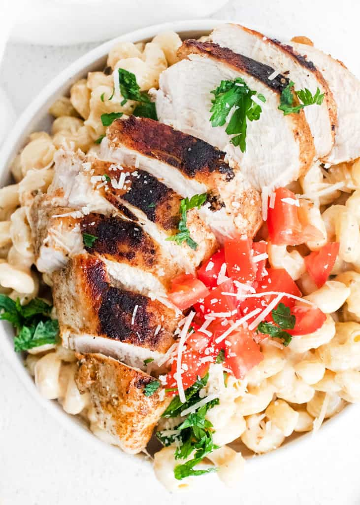 cajun chicken breasts sliced over alfredo pasta topped with parmesan and tomatoes