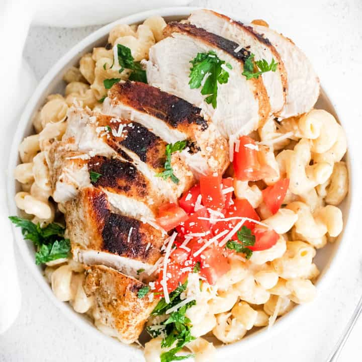 cajun chicken breasts sliced over alfredo pasta topped with parmesan on white table