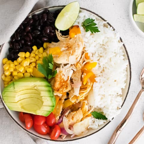 pressure cooker chicken fajita bowls on table with spoons and lime wedges