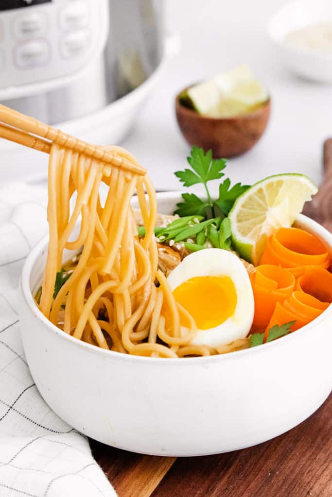 Chicken Ramen noodles picked up by chopsticks