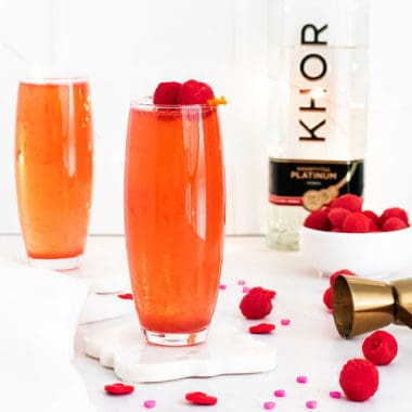 Raspberry Rosé Spritzer on table with bottle of vodka