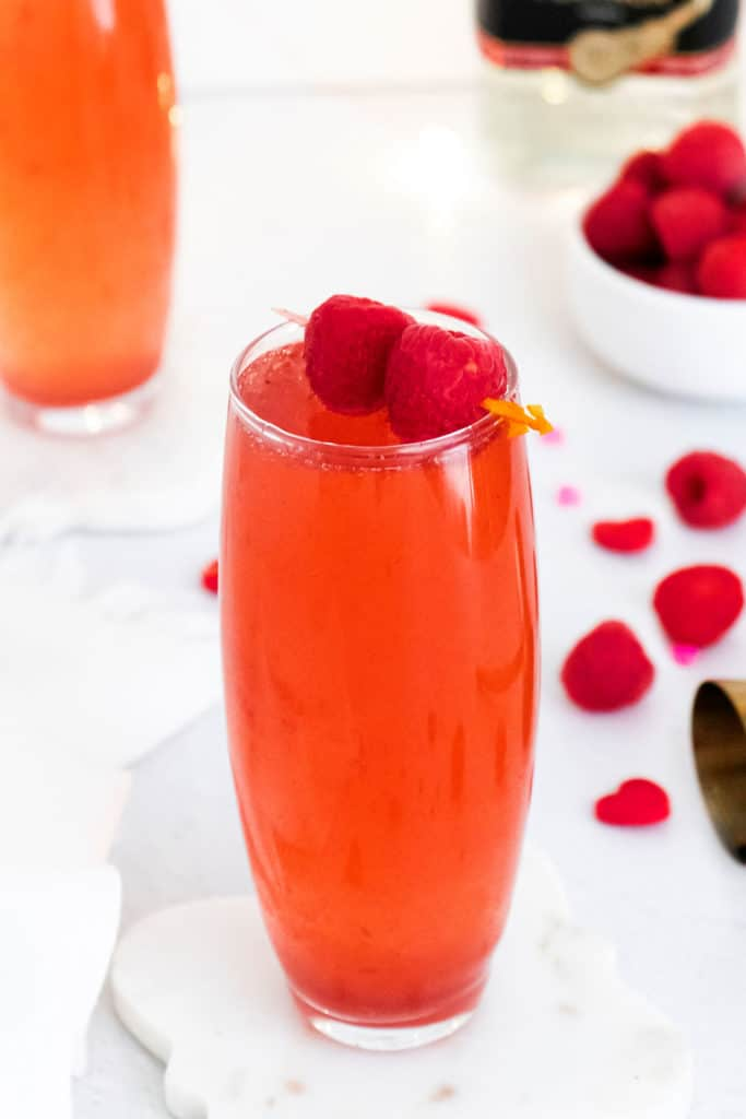 Raspberry Rosé Spritzer topped with raspberries on toothpick