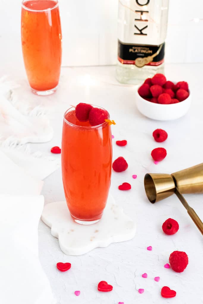Raspberry Rosé Spritzer on table with shot pourer and bowl of raspberries