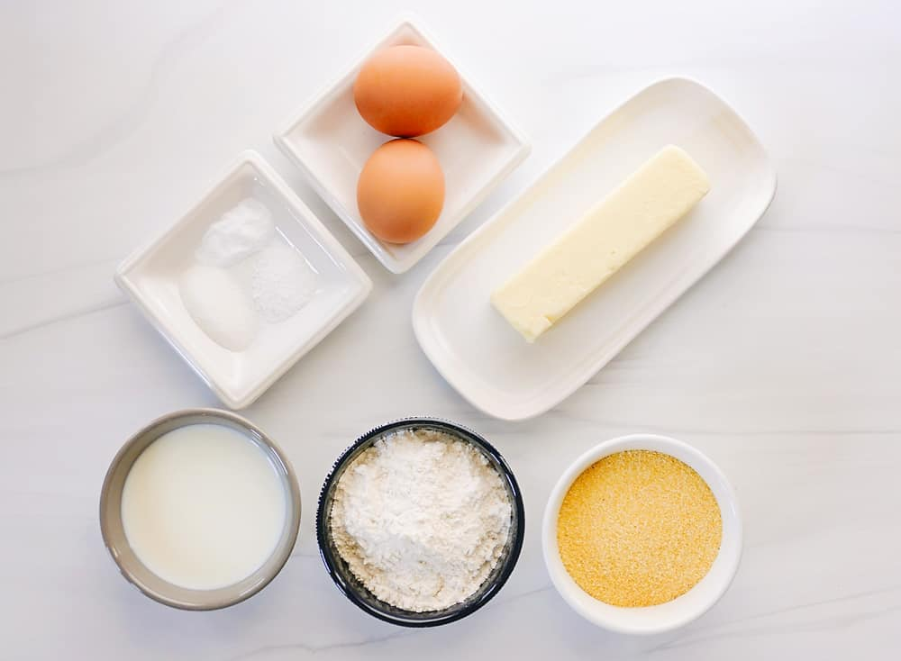 ingredients for cornmeal pancakes on white table