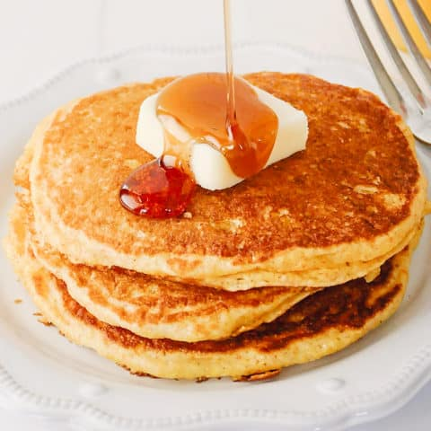 syrup being poured on cornmeal pancakes