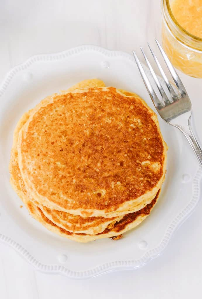 stack of cornmeal pancakes on white plate