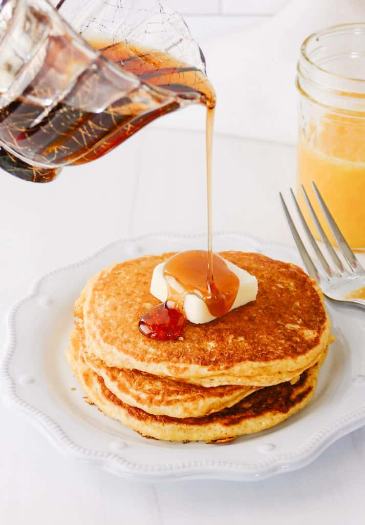 syrup being poured on cornmeal pancakes with butter