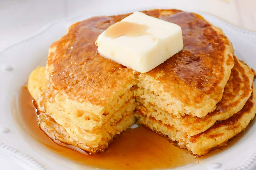 cornmeal pancakes topped with butter and syrup and bite taken out