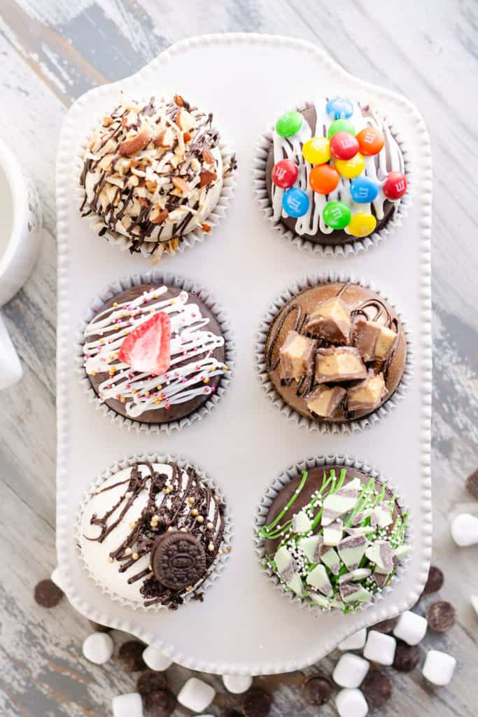 variety of hot cocoa bombs in muffin tin with hot chocolate mix