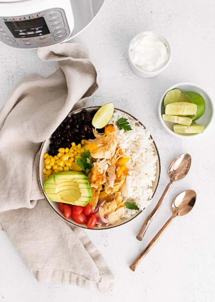 Instant pot chicken fajitas in white bowl on table with pressure cooker