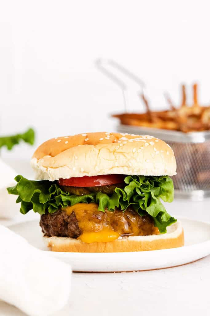 air fryer cheeseburger on plate served next to fries