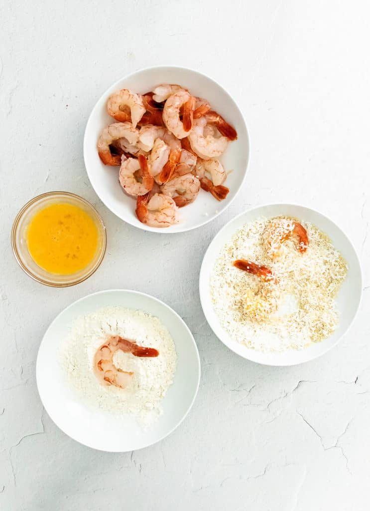 Raw pink shrimp, panko & coconut, flour and eggs in bowls on table