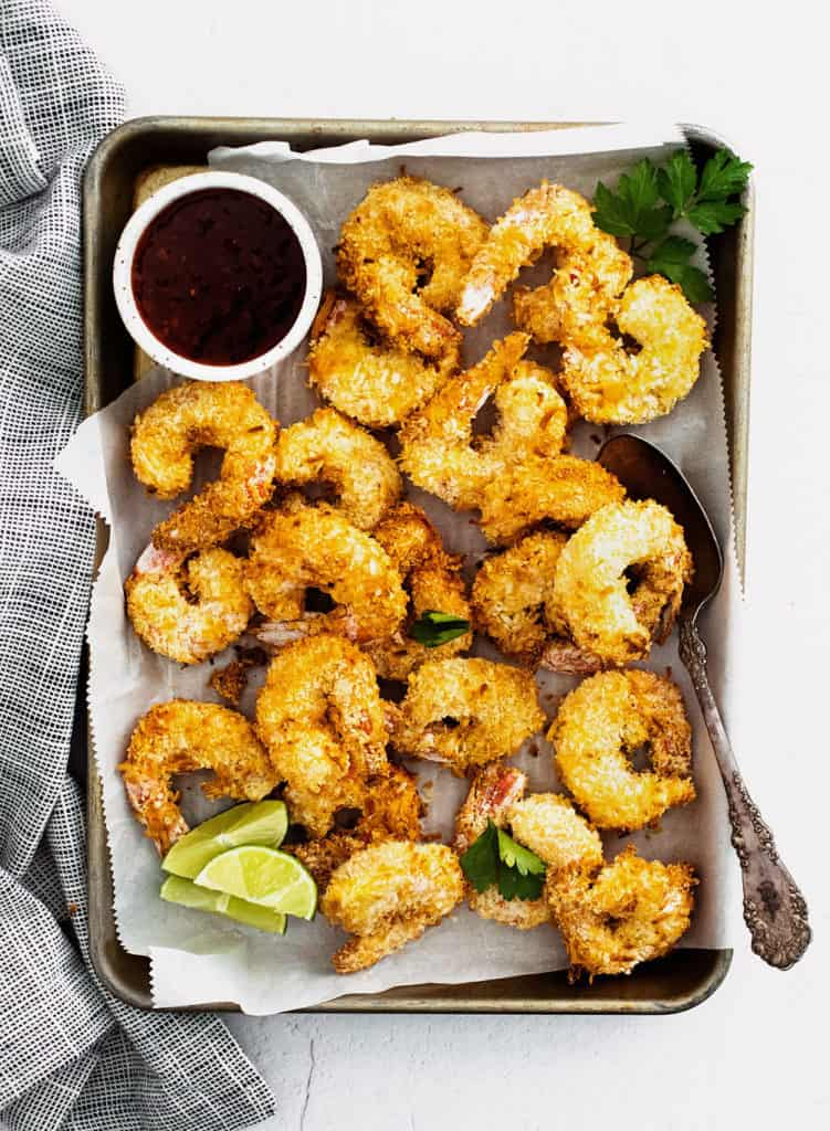 coconut shrimp on sheet pan with parchment with limes and sweet chili dipping sauce