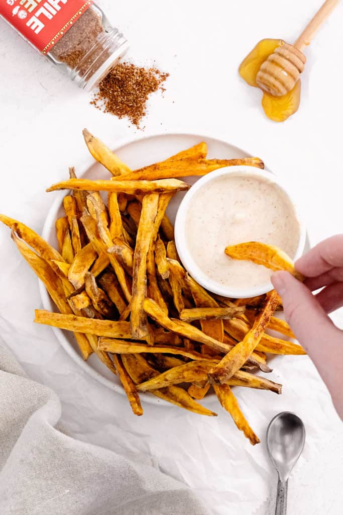 sweet potato fries being dipped into yogurt dipping sauce