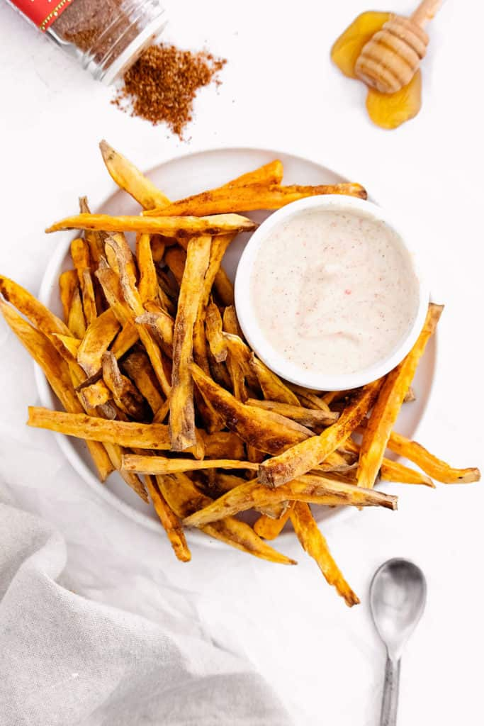 sweet potato fries on white plate with yogurt dipping sauce