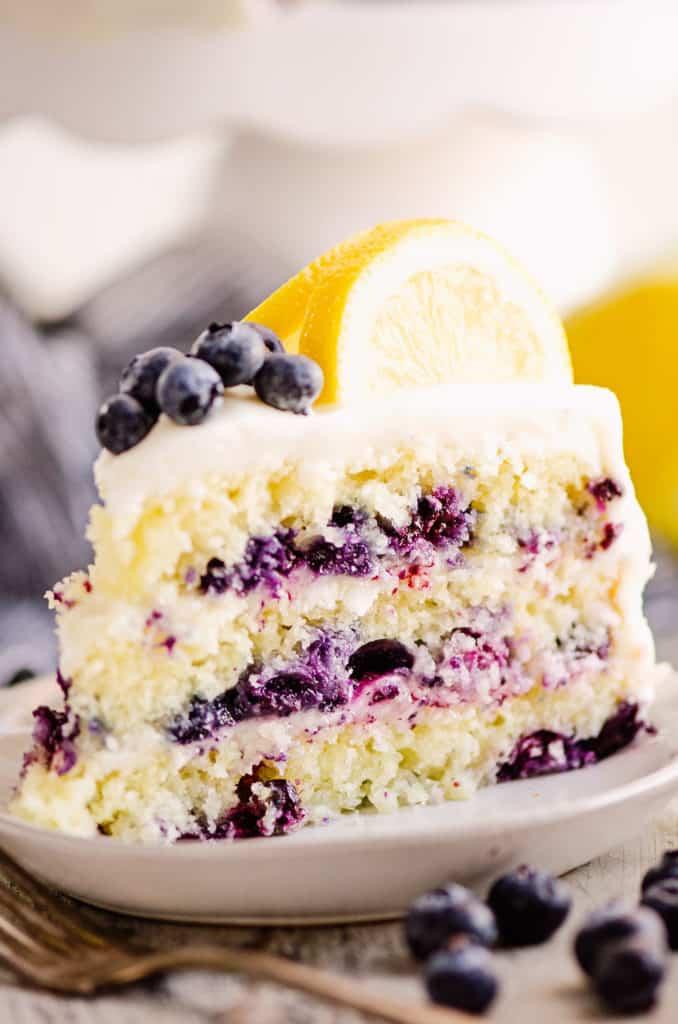 slice of layered blueberry lemon cake on plate