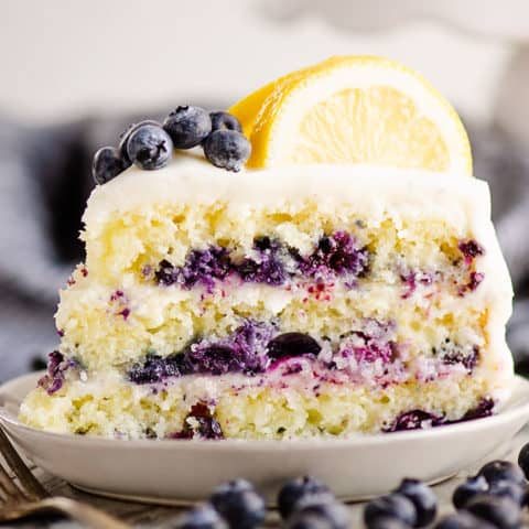 slice of lemon cake on plate with blueberries on table