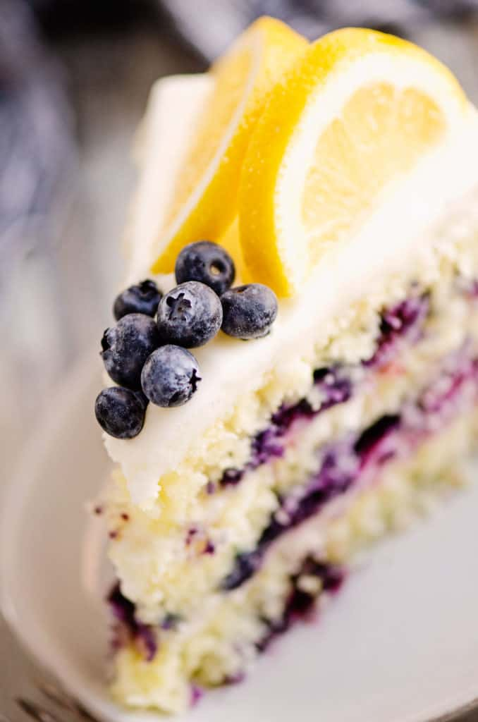 slice of layered cake topped with blueberries and fresh lemons