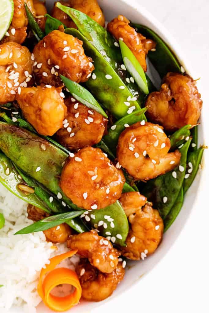 sesame shrimp, carrots and peas in white bowl