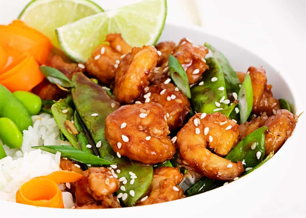 sesame shrimp and vegetables in white bowl with lime wedges