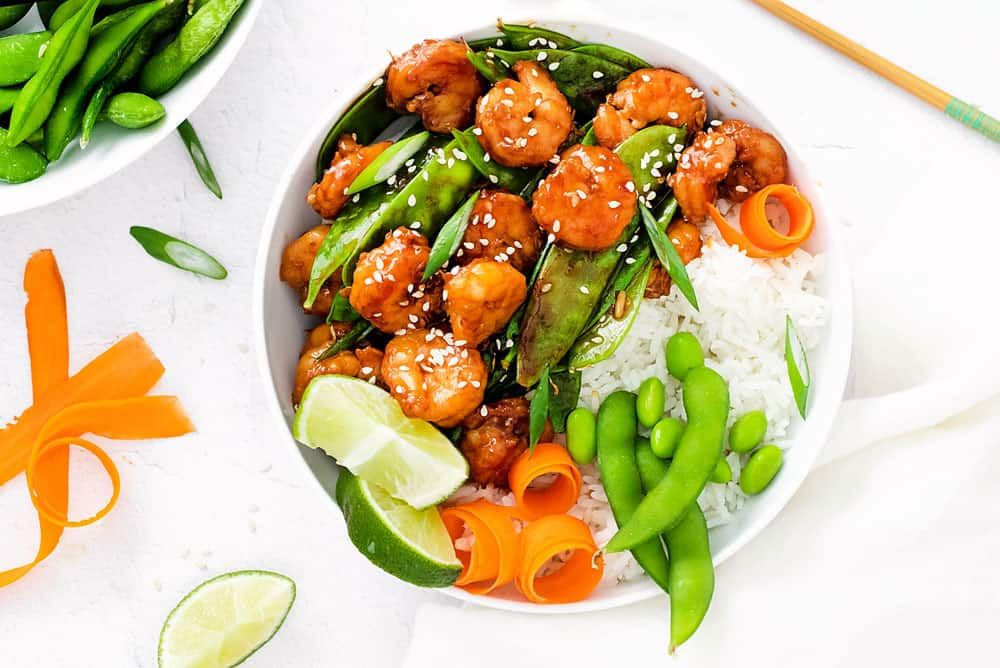 edamame, carrots, rice, lime, peas and shrimp in bowl with chopsticks