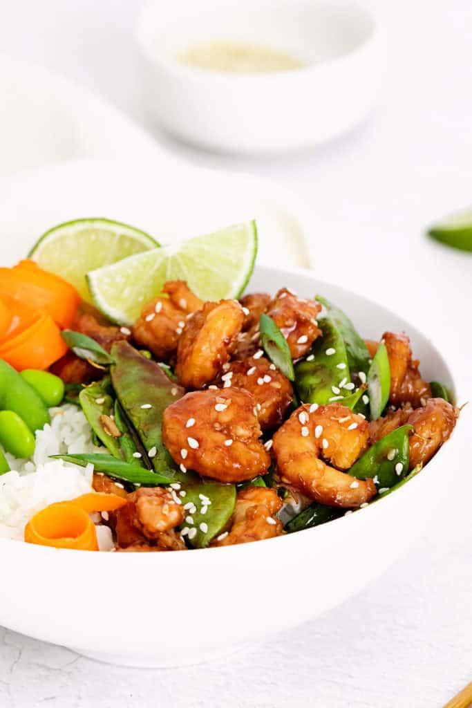 sesame shrimp, peas and carrots in white bowl