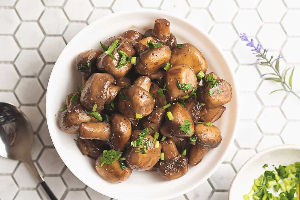 sauteed mushrooms topped with parsley in white bowl