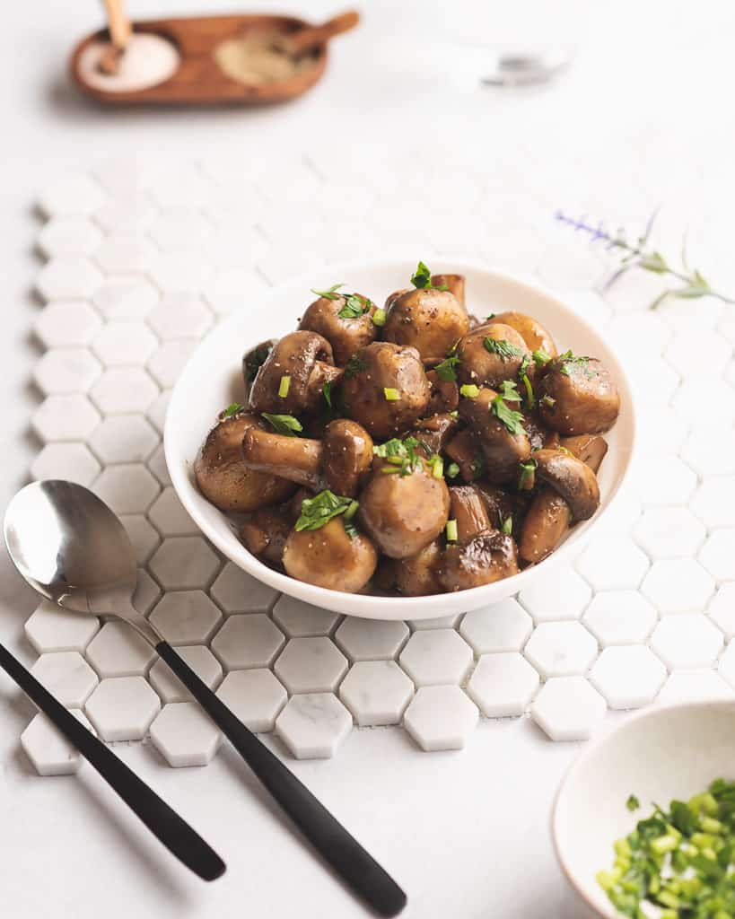 sauteed mushrooms on table with tile and utensils