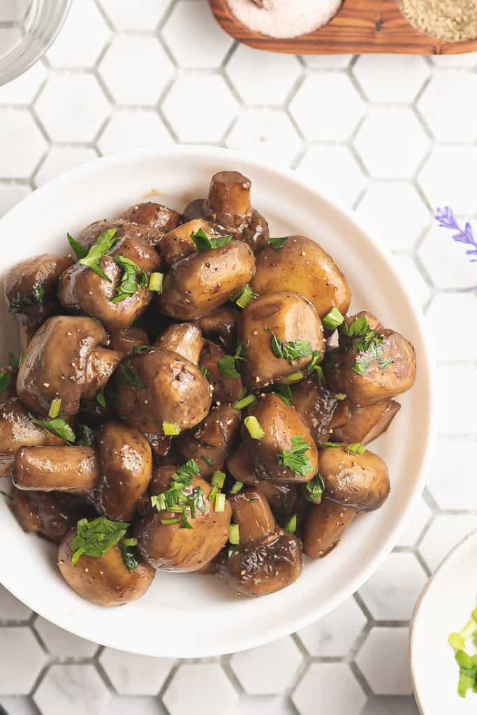 fresh mushrooms topped with parsley on tile table