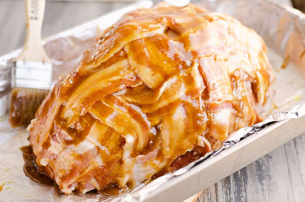 bacon wrapped ham with maple glaze in roasting pan