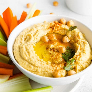 creamy classic hummus in white bowl topped with chickpeas