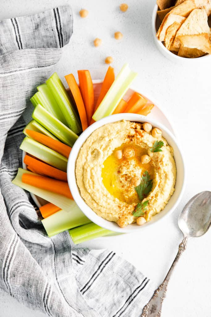 plate with bowl of classic hummus, vegetables on table with bowl of bread and spoon