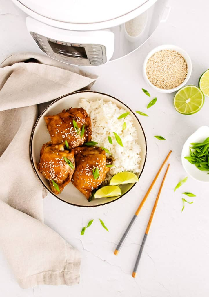 honey soy glazed chicken thigh in bowl with lime wedges, rice and sesame seeds