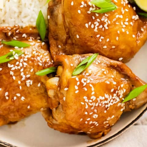 honey soy glazed chicken thighs garnished with sesame seeds and green onions