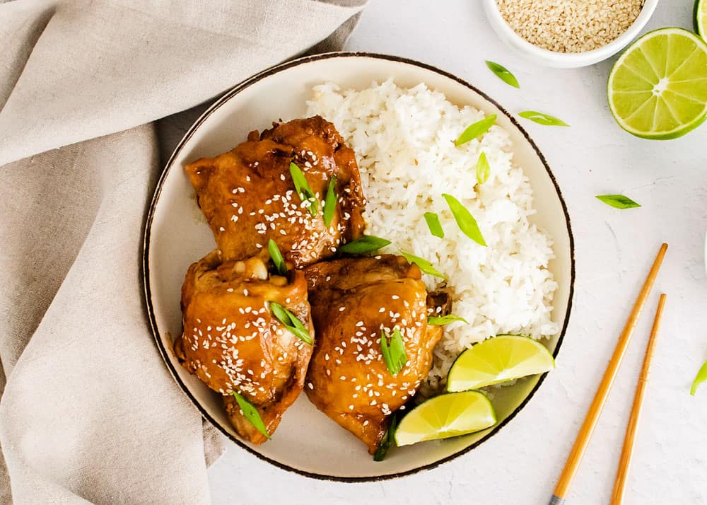 honey soy glazed chicken thighs in bowl with rice on table with chopsticks