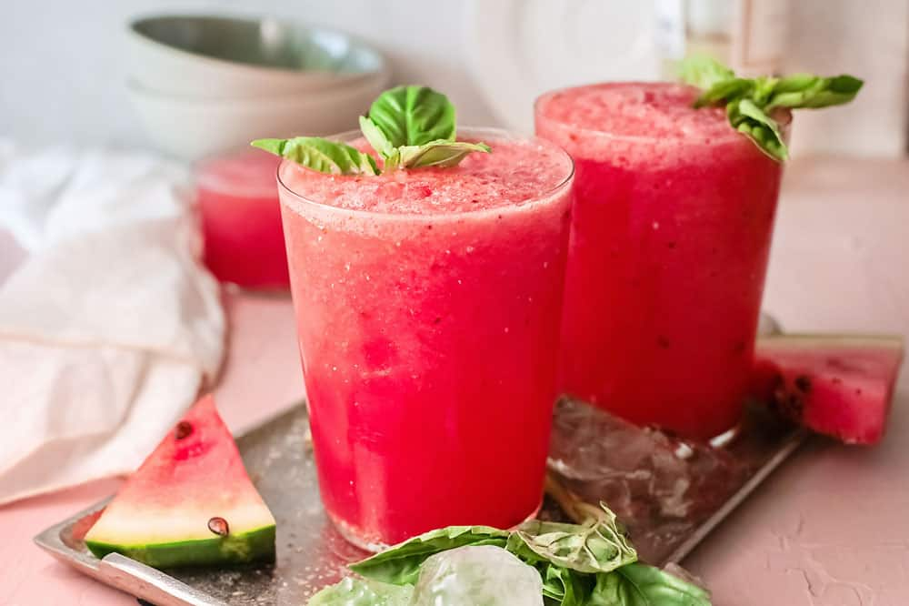 watermelon wine slushies on tray with watermelon wedges and ice