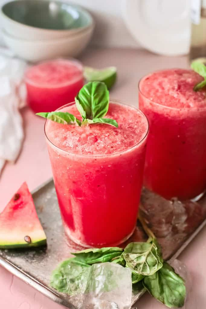 watermelon wine slushies on table with basil leaves and watermelon wedges