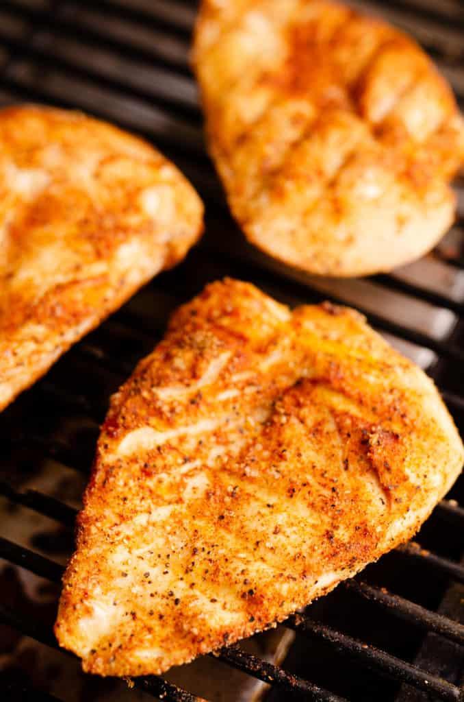 seasoned chicken breasts on smoker grill