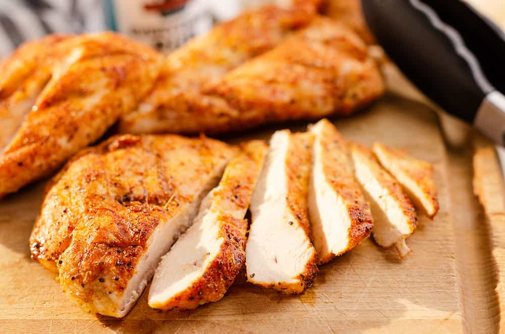 grilled chicken breast sliced on cutting board