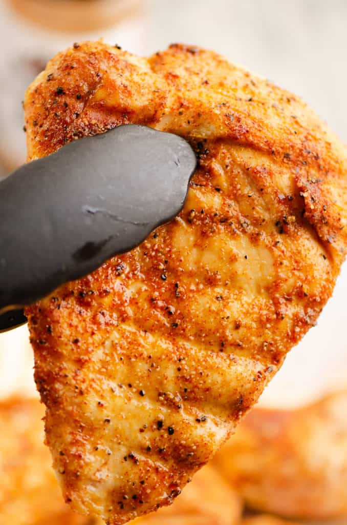 smoked chicken breast in tongs