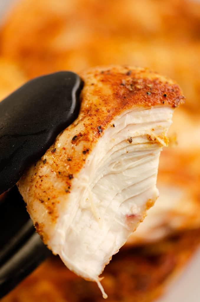 half chicken breast in tongs