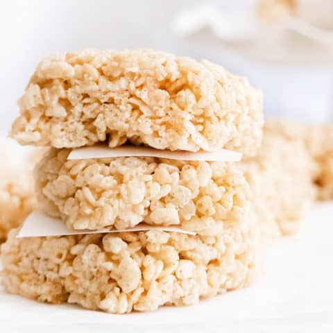brown butter rice krispie treats stacked with parchment paper