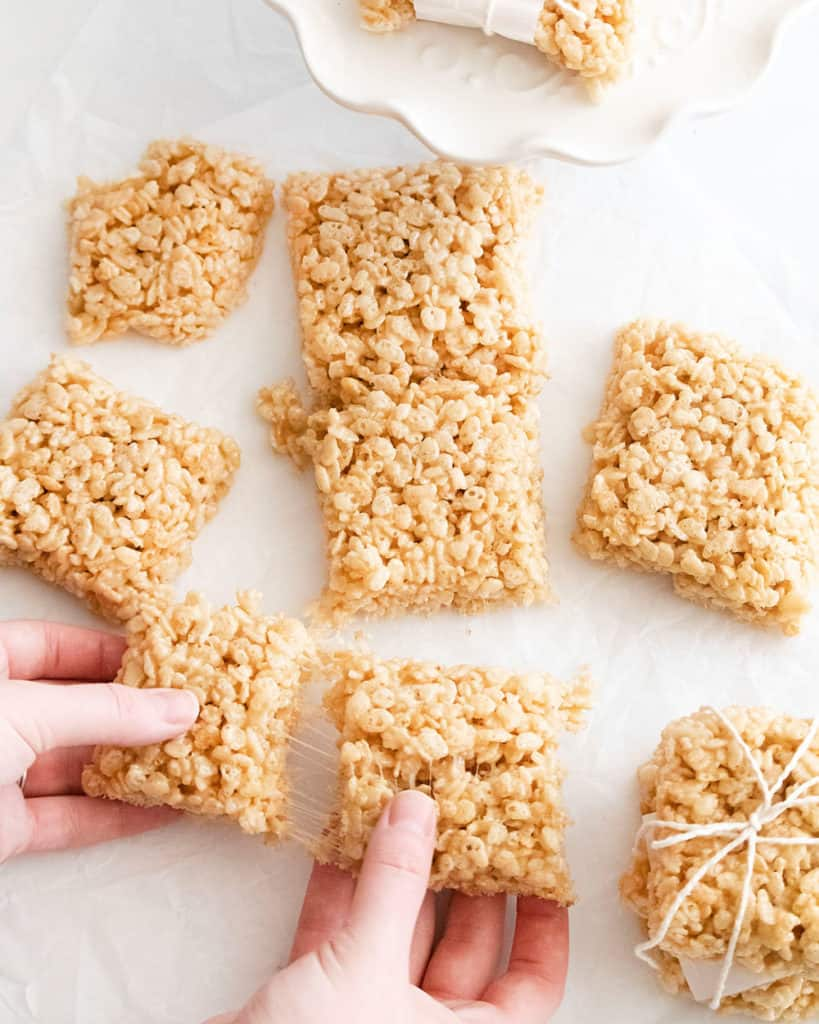 brown butter rice krispie treats on table and hands pulling two bars apart